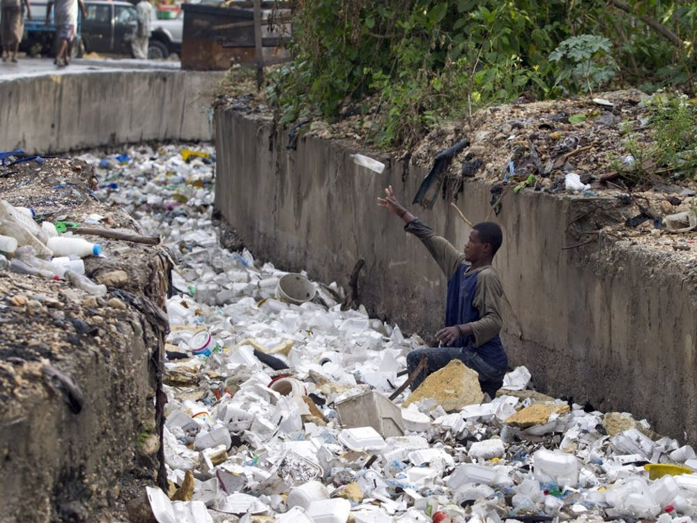 A young man sifts through the trash in a small canal near downtown Port au Prince, Haiti, looking for recycleables two days after Tropical Storm Isaac brought rains and heavy winds across Haiti in August 2012. Among the trash are styrofoam lunch containers that will soon be banned in Haiti. (Patrick Farrell/Miami Herald/MCT)