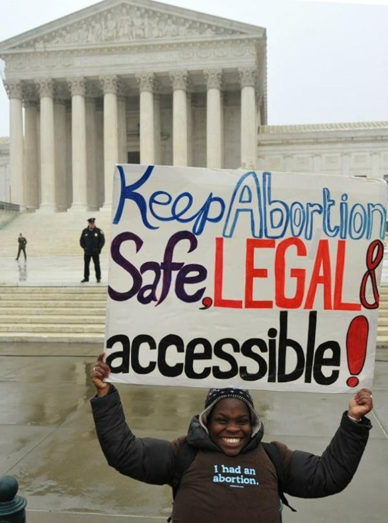 Woman poses in front of the SCOTUS building in Washington D.C. in 2012.Photo by Debra Sweet on Flickr.