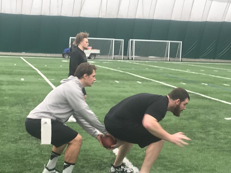 Tyler Wiegers and Dakota Tallman practice snapping the ball in the indoor practice facility on March 22.