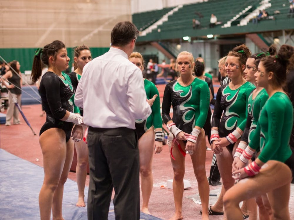 Eastern Michigan head coach Jay Santos talks to his bars rotation in the Eagles 3rd place finish in their Quad Meet in East Lansing on March 6 2015.