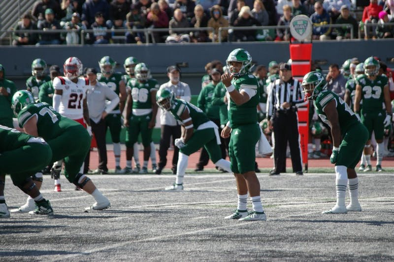 EMU quarterback Mike Glass III motions a receiver at Rynearson Stadium on Oct. 12.