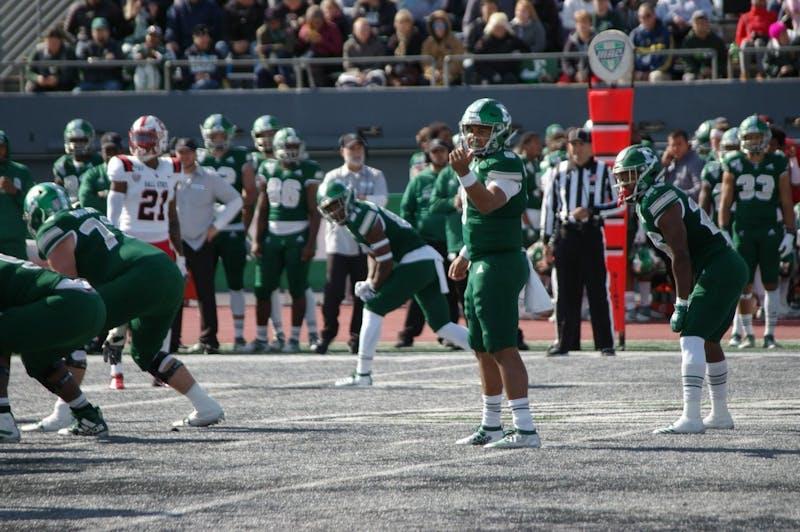 EMU quarterback Mike Glass III motions a receiver at Rynearson Stadium on Oct. 12.