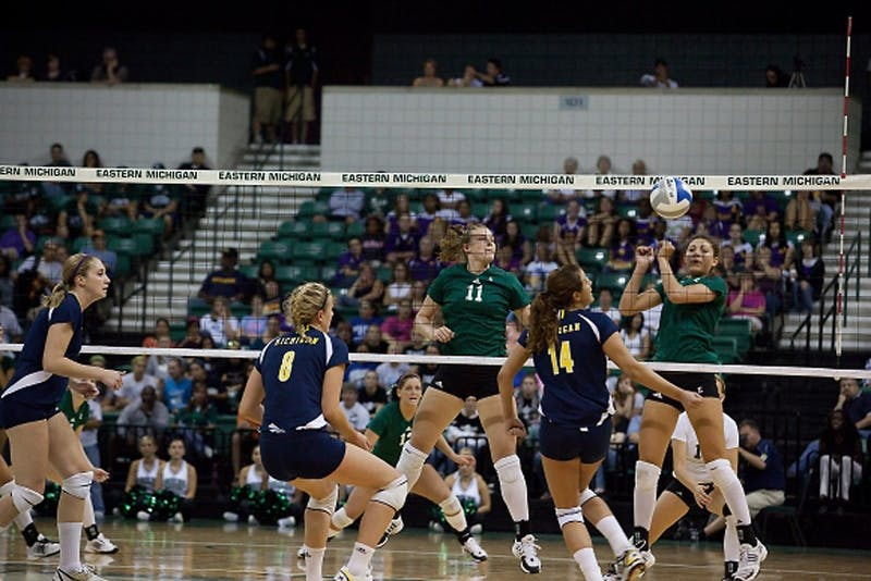 EMU's Jennifer Swartz (11) watches as her teammate Rachel Iaquaniello hits the ball to the opposing Michigan side for a point.