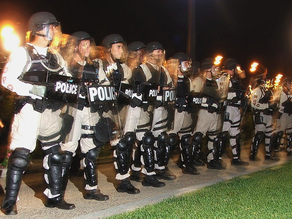 Riot police surround the perimeter of Schenely Park during an anti-police brutality demonstration.