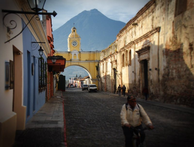 A man cycles on road during the daytime in Antigua Guatemala, Guatemala. Photo by Jeison Higuita on Unsplash.