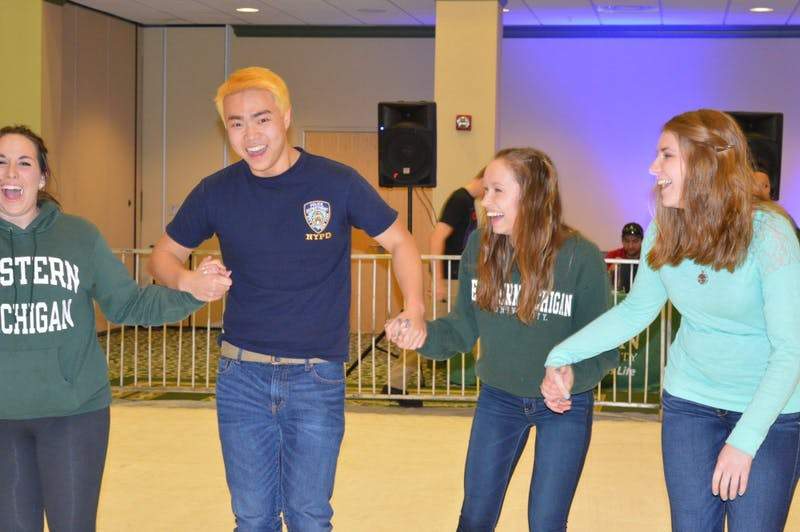 Students hold on to each other for balance while ice skating in the Student Center Ballroom.