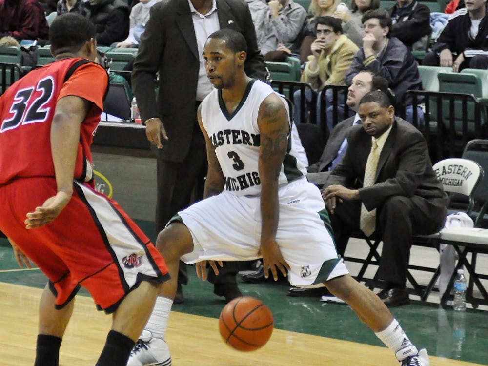Carlos Medlock (3) dribbling Saturday with coach Charles Ramsey closely watching. Medlock had a career-high 32 points in the game.