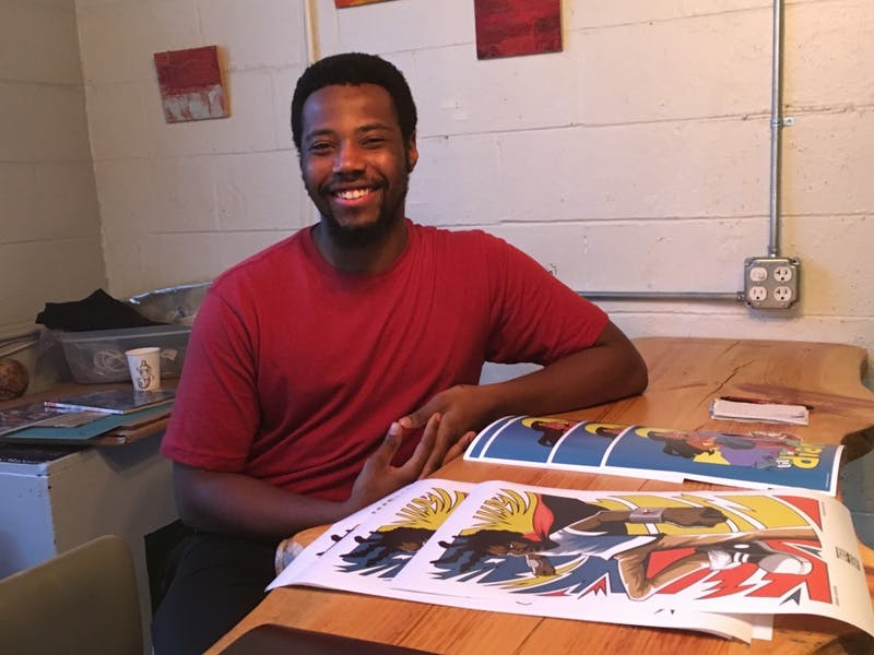 """Jermaine Dickerson is a Freelance Graphic Designer and Illustrator, seen at the""""The Ugly Mug"""" for Ypsilanti Art Walk."""