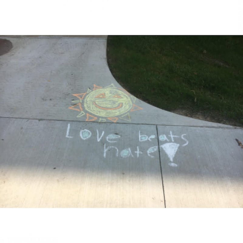 Chalk drawing and message inspired by Alpha Phi Omega.