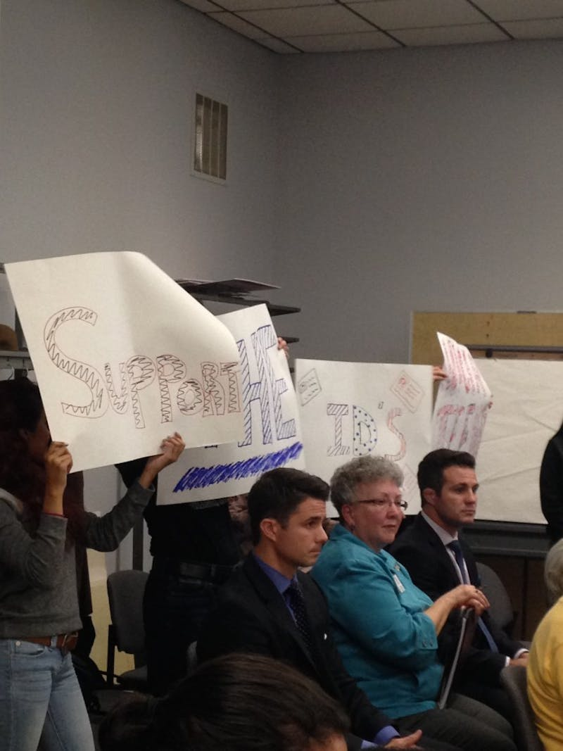 Youth hold signs supporting the Washtenaw ID Project at the Oct. 7 Ypsilanti City Council meeting. Photo by: Allie Tomason