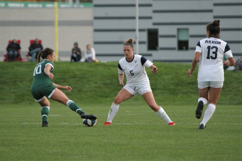 Akron defender Abigail Brown sets up against EMU's Sabrina McNeill at Scicluna Field on Oct. 24.