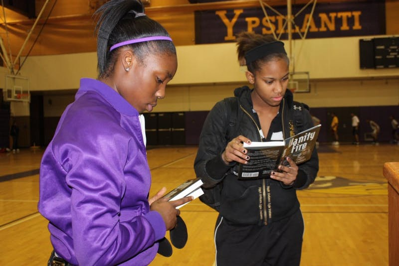 Carneysha McGee, left, and Cassandra Gibson select a few books during the Dec. 10 Book giveaway at Ypsilanti High School sponsored by the Michigan Education Association and the NFL.