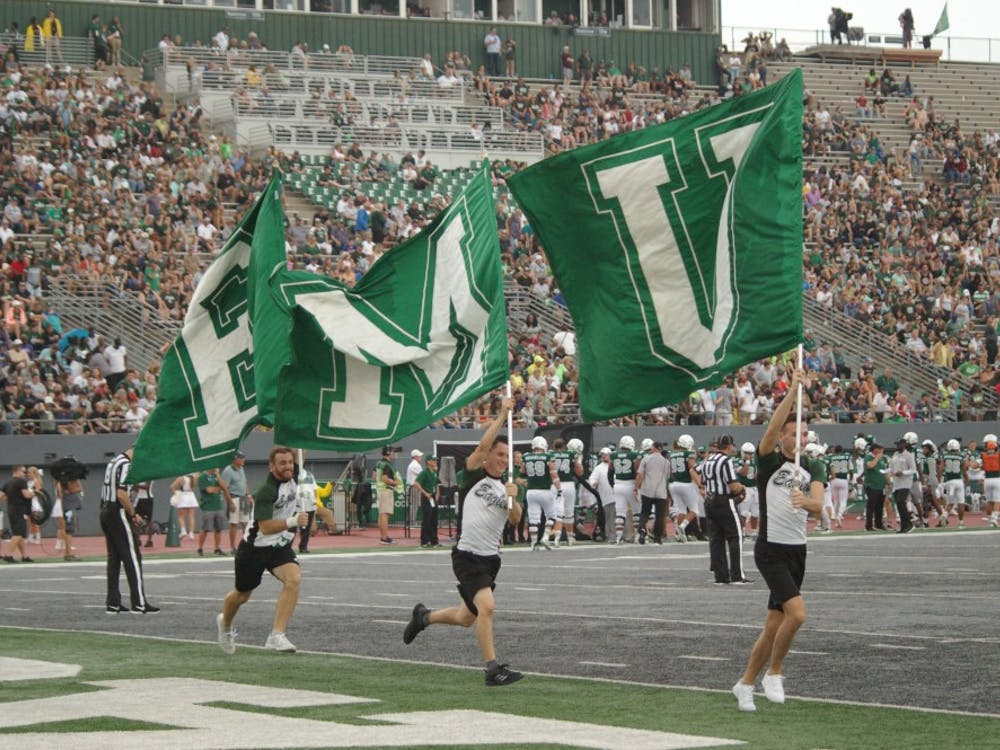 EMU flags are ran through endzone at Rynearson Stadium.