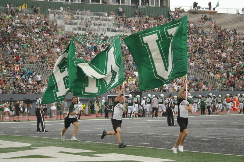 EMU flags are ran through endzone at Rynearson Stadium on Sept. 21.
