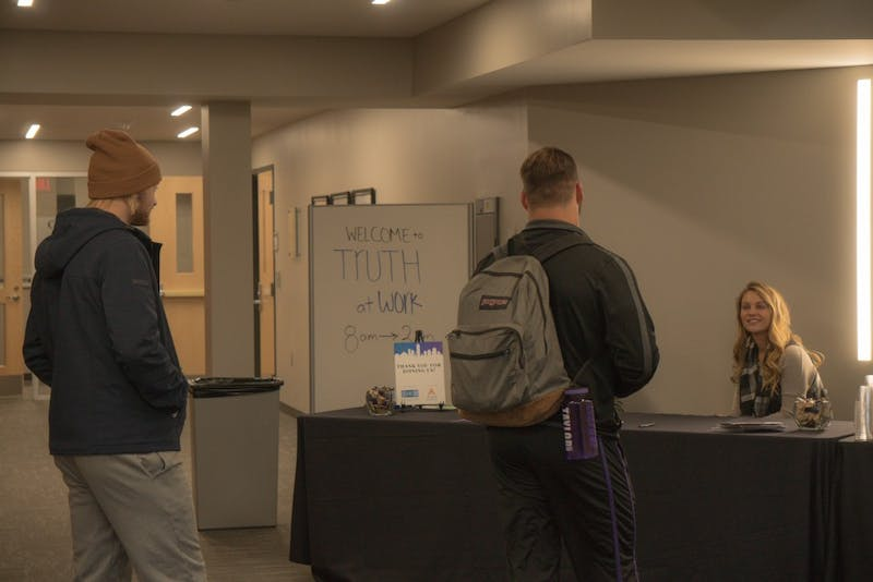 Sam Bartu and Zac Saltzgaber sign in to attend the Truth at Work Conference.