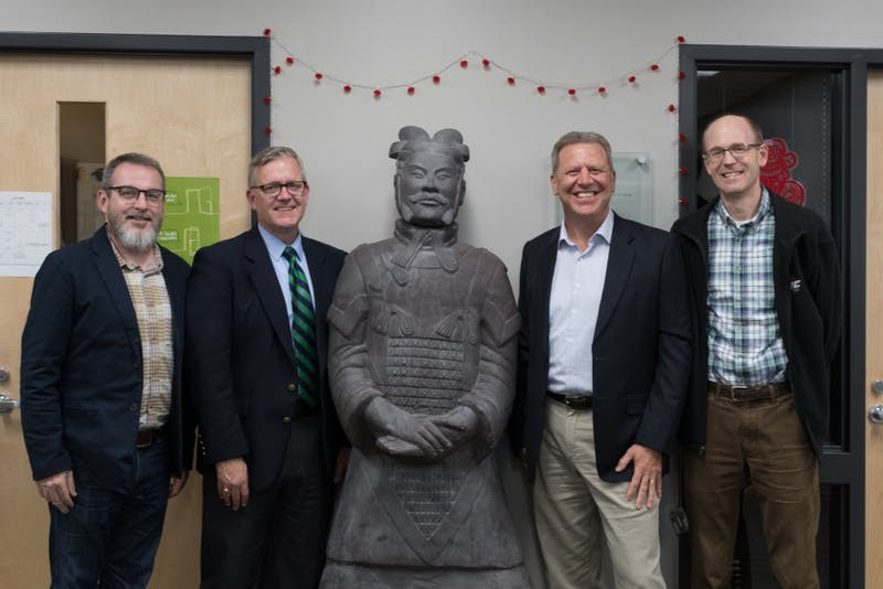 Jeff Cramer, Michael Hammond, Charlie Brainer and Greg MaGee pose next to the Terra Cotta Warrior located in the Spencer Center.