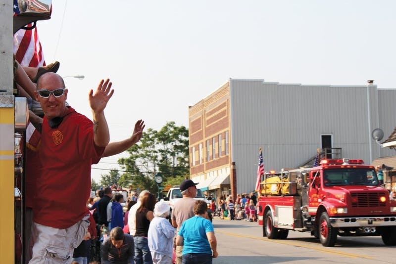 A local firefighter waves at the crowd as the fire engines advance down the streets of Upland. (Photograph by Hannah Bolds)