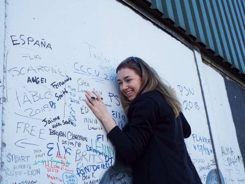"Junior Sarah Brennan writes ""Taylor University Spring 2018"" on Peace Wall in Belfast."