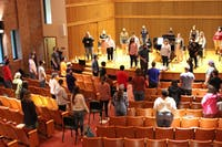 Taylor Chorale students hold rehearsals in the recital hall while maintaining distance by utilizing the stage, aisles, and seats. (Photo by Anna Collins)