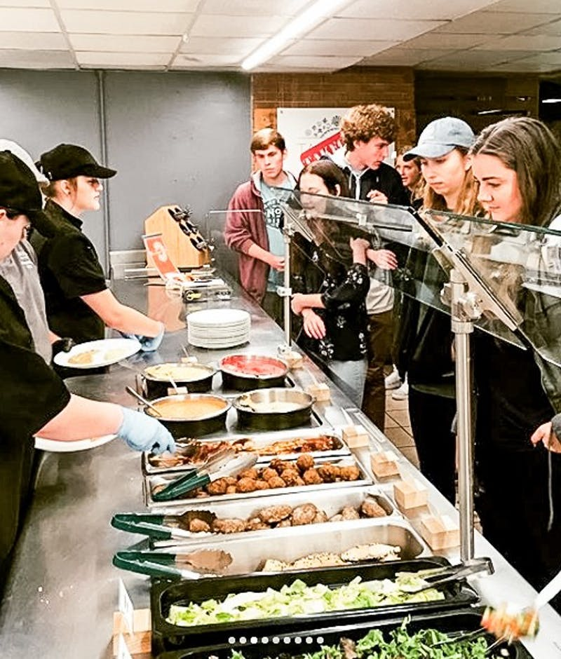Students wait in line to get food from the Za'atar hummus bar that has taken over the Taqueria station.