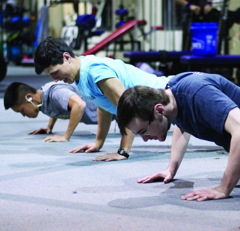 (L to R) Senior Jonah Bourassa, freshman Jack McNeil and sophomore Jed Barber do push ups together. (Photograph by Ross Kimbrell)
