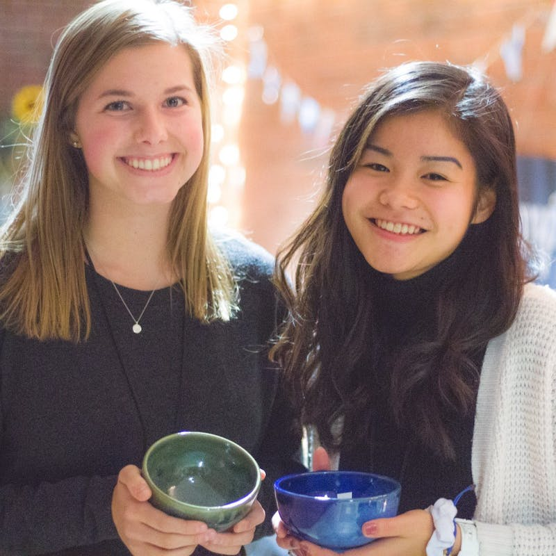 Sophomore Leigh Sumner and Freshman Angela Loh show off their bowls before filling them with soup.