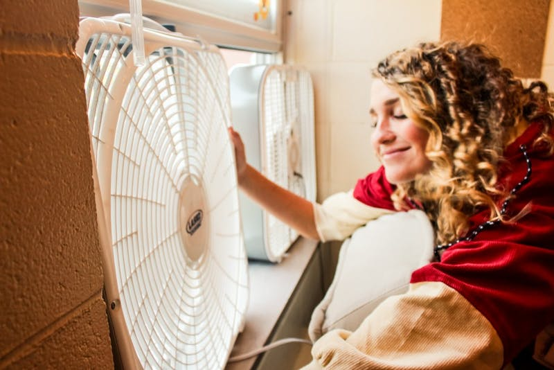 Sophomore Chloe Sohmer uses a fan to cool down inside Olson Hall.