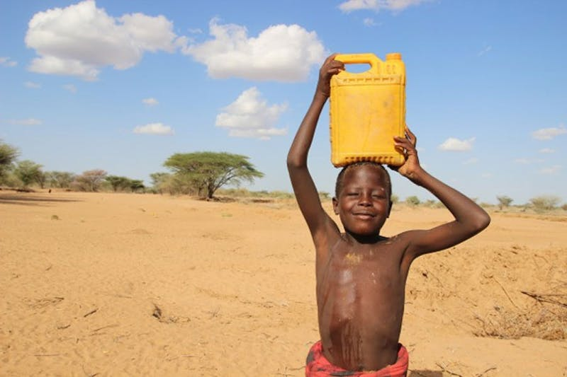 A young boy carries a yellow jerry can of water on his head from the new well in Nigeria. (Photo provided by Debbie Zancanaro)