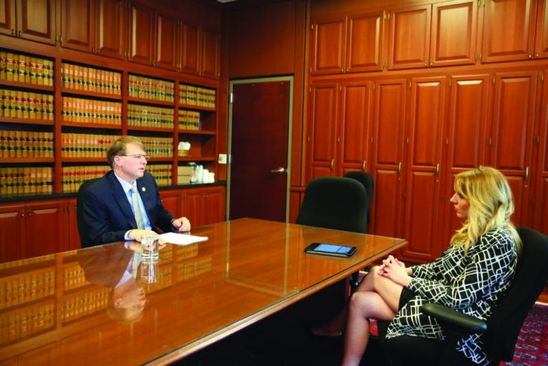 North Carolina Supreme Court Chief Justice Mark Martin speaks with Carolina Journal Associate Editor Kari Travis ('14) in his Raleigh, North Carolina, offices during a July 2017 interview. (CJ photograph provided by Don Carrington)