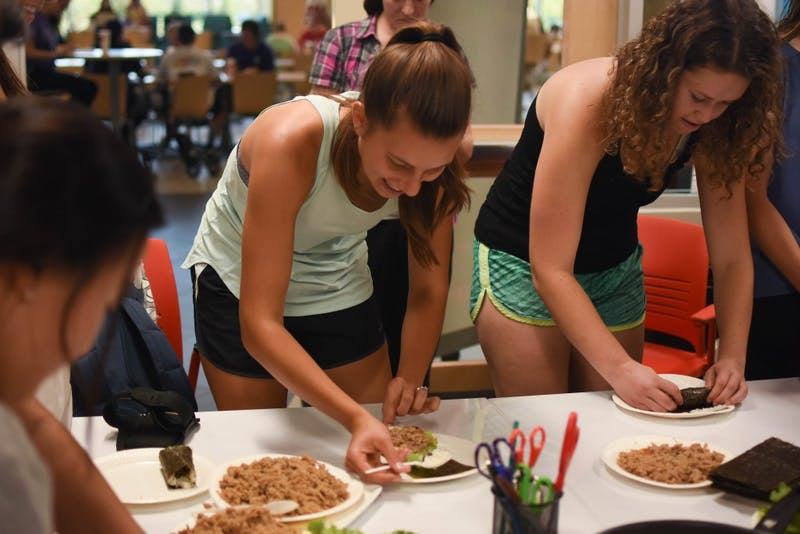 Seniors Karolina Kahle and Gwyneth Terrett explore cultures at Kimpap Night on Sept. 19.