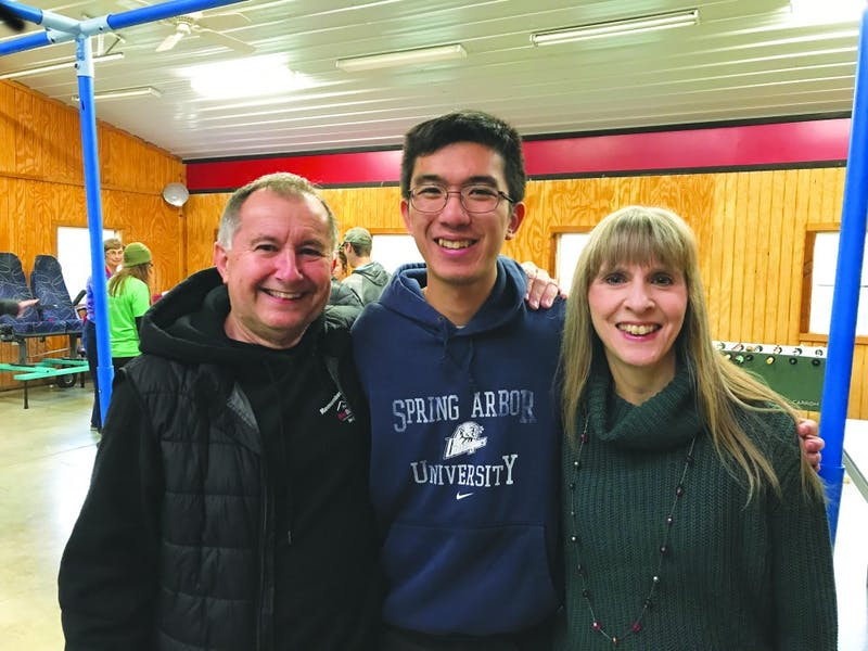 Senior Chester Chan (center) enjoys volunteering his time for the RedBarn directors Troy Shockey (left) and Liz Shockey (right). (Photograph by Braden Ochs)