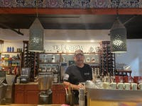 Gordon Jackson stands behind the bar in his glass factory turned coffee shop.