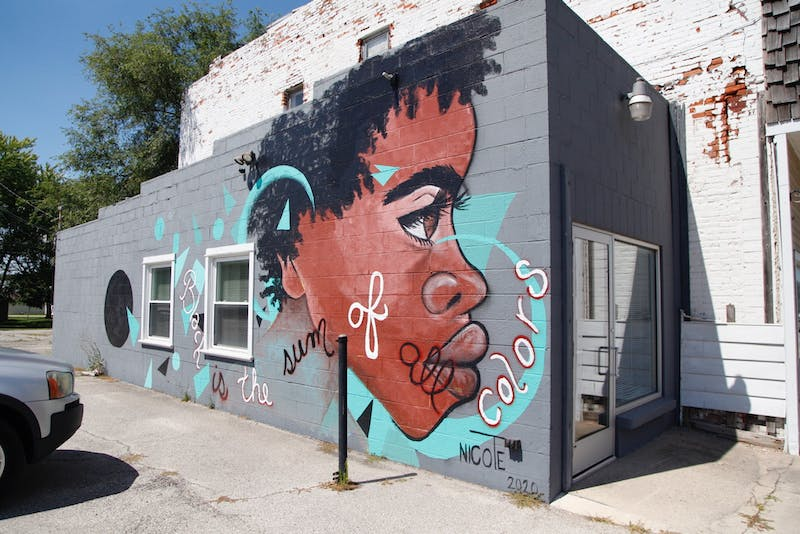 Tashema Davis, an artist based out of Gary, Indiana, creates a mural in memory of recent Black Lives Matter protests that are taking place nation-wide. (Photo by Lauren MacDonald)