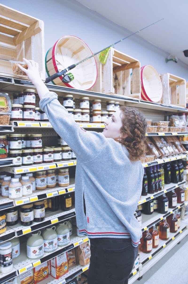 Freshman Zoe Mendenall reaches for pretzels in the newly branded Walnut Creek Country Market. (Photo by: Avery Amstutz)