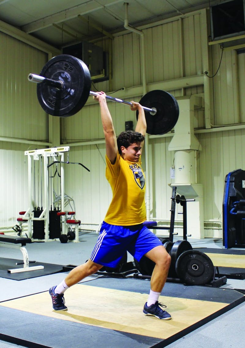 Sophomore Daniel Black pushes through another set of hanging snatches. (Photograph by Riley Hochstetler)