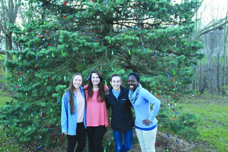 Sophomores Leah Metzger and Josie Luptak, junior Crysta Haynes, and senior Kaylise Taylor stand in front of the Upland Christmas tree that will be lit this Sunday in Depot Park. (Photograph by Ellie Bookmyer)
