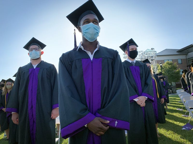 Class of 20' masks up on the lawn between Euler Science Complex and Reade Center for an outdoor graduation.