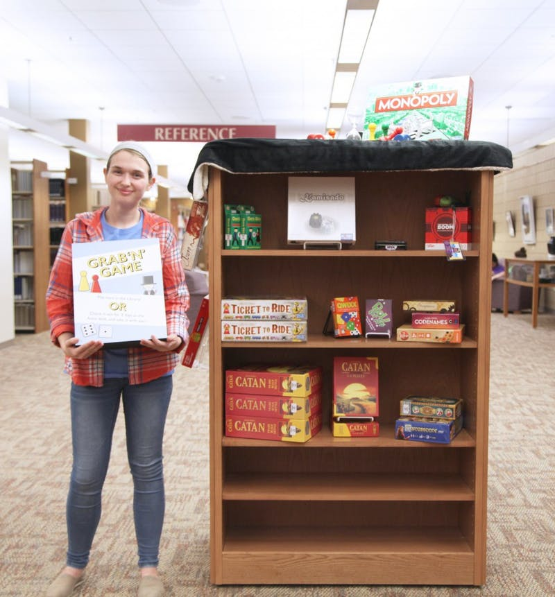 Junior Kait Bedel shows off Zondervan's display of games for checkout. (Photograph by Gabby Carlson)