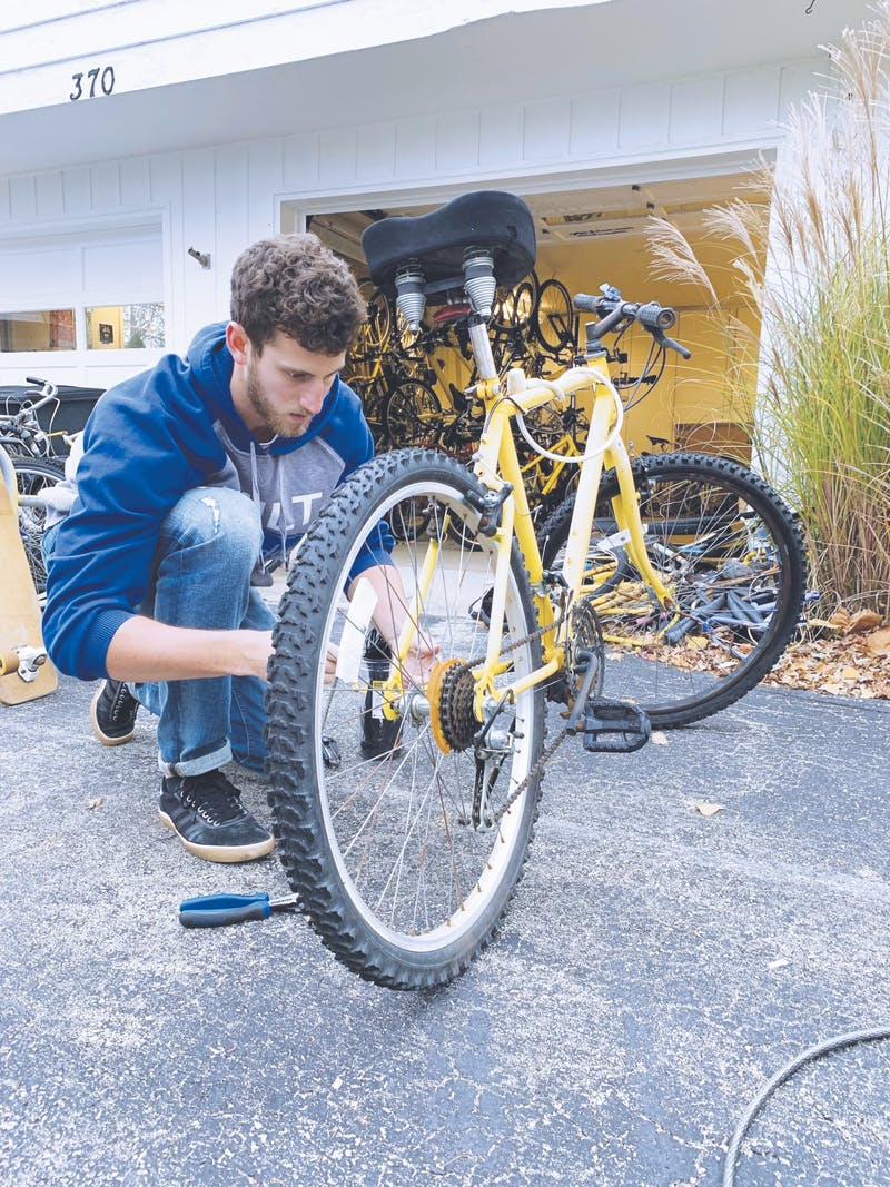Junior Matt Wildman preps bikes before they're distributed to residence halls. Bikes are now available for rent at front desks.