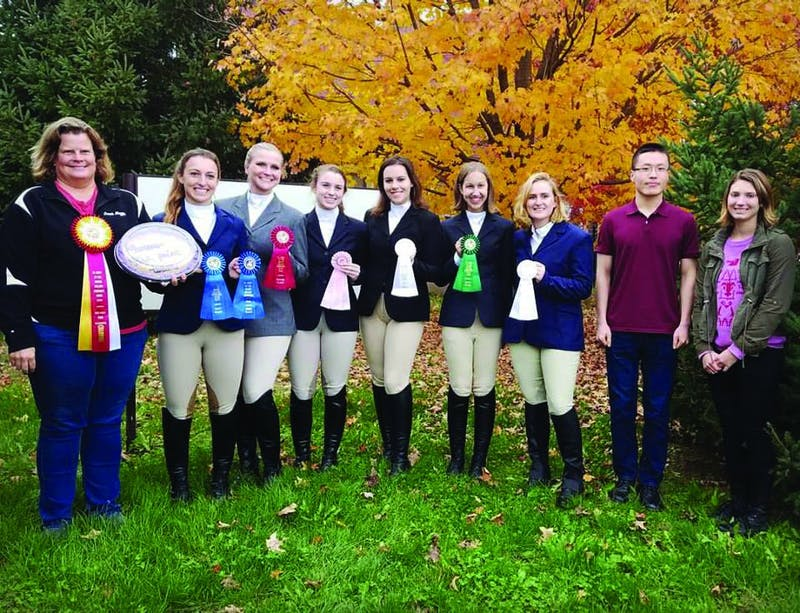 The equestrian team poses with the awards they won at a competition. Their awards are proof of all the hard work they put into training.