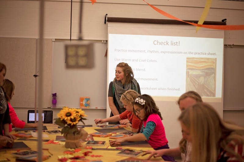 "Junior Kaitlyn Weaver watches her fifth and sixth grade art students recreate Edvard Munch's painting ""The Scream."""