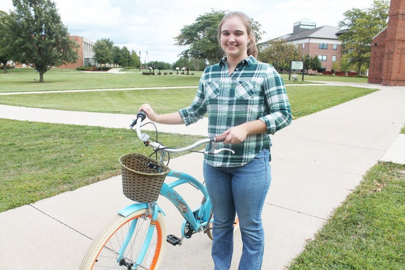 Sophomore Alyssa Roat poses with her mended bicycle. (Photograph by Halie Owens)