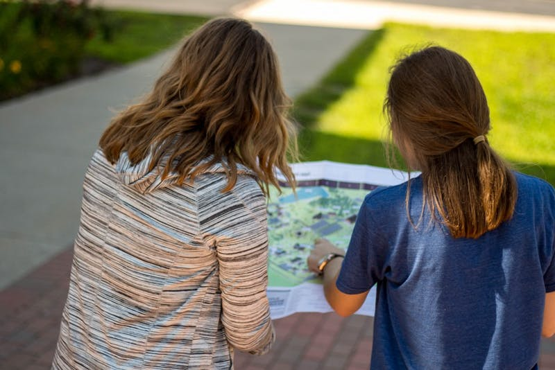 Elizabeth Hammond (R) and Lindsay Rice (L) study the map of campus in search of their next destination. (Credit: Kassie Joviak)