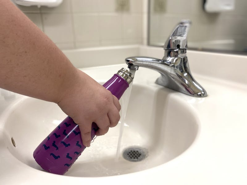 Student fills up their water bottle in the dorm bathroom