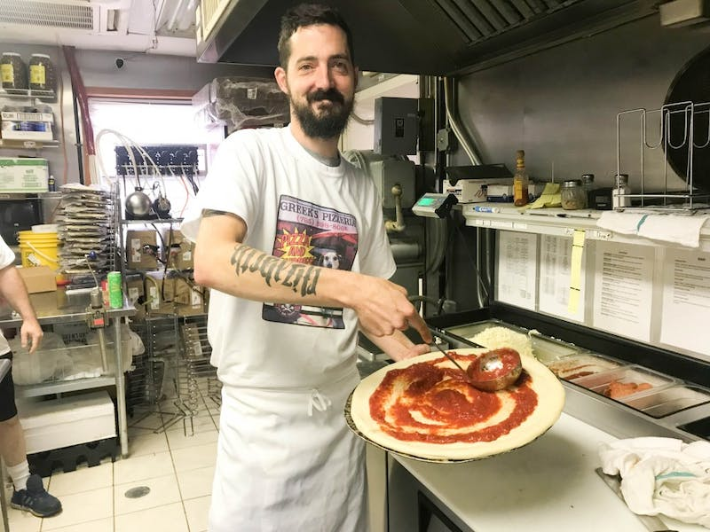 Drew Kemp, the general manager of Greek's Pizzeria in Upland, prepares a pizza for one of his customers. Kemp arranged the event at Greek's to give back to the volunteers of the Blackford County Animal Shelter.