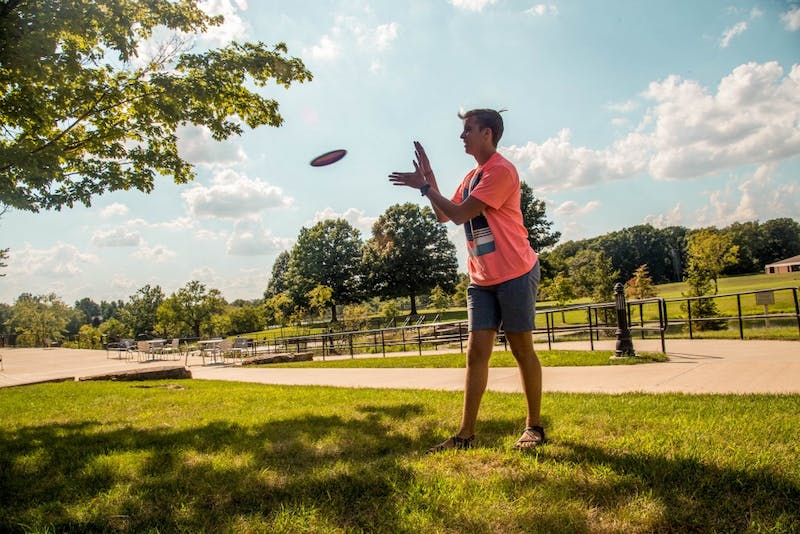 Junior Andrew Freer catches a disk on Breuninger lawn.