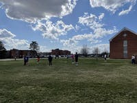 Students play soccer outside on the lawn.