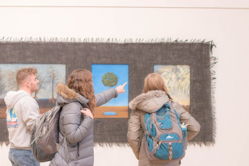 Students observe the apocalyptic group of illustrations in the art exhibit(Photograph by Ben Williams)