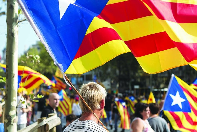 Demonstrators take to the streets of Barcelona, waving Catalonian flags. (Photograph provided by Wikimedia Commons.)
