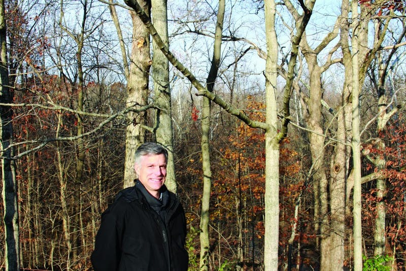 Professor Ed Meadors poses with his tree farm that he has been growing for almost 20 years. (Photograph by Ellie Bookmyer)